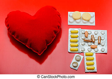 Red heart and pills on red background