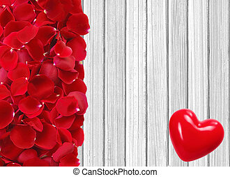red heart and rose petals on white wooden background