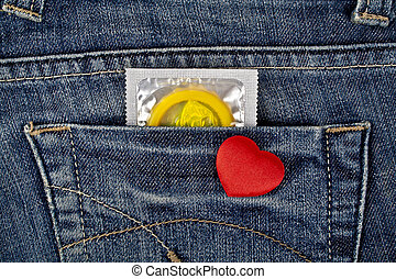 Red heart and yellow condom in blue jeans pocket