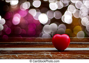 Red heart ball on wood table with light bokeh background.