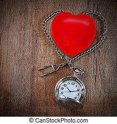 Red heart ball with vintage pocket watch on wood backround.