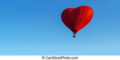 Red heart balloon on blue sky