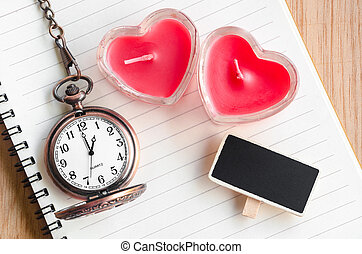 Red heart candle and pocket watch.