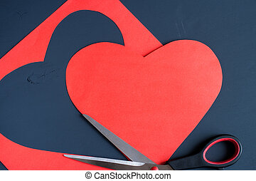 Red heart carved from paper sheet and steel scissors on dark painted background.