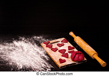 Red heart cookie and a piece of dough on the wooden board, baking for Valentine's Day