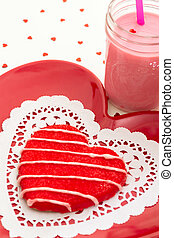 Red heart cookie on red plate decorated for Valentine's Day