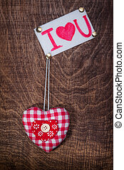 Red heart fabric and the sheet with the inscription on a dark brown background. Valentine's day.