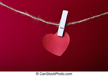 Red heart hanging on line against red background.