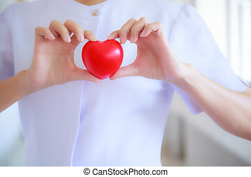 Red heart held by smiling female nurse's hand, representing giving effort high quality service mind to patient. Professional, Specialist in white uniform concept