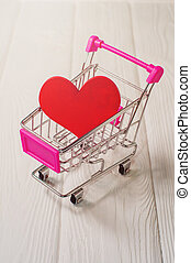 Red heart in a mini supermarket trolley on a white wooden table. Love shopping concept. Discounts and sales on a black Friday. Gift on Valentine's Day.