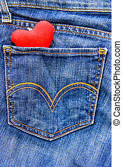 Red heart in a pocket of blue jeans