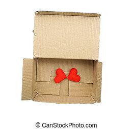 Red heart in an open cardboard box