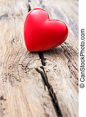Red heart in crack of wooden plank