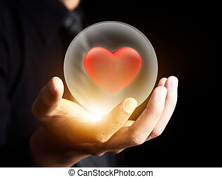 Red heart in crystal ball - Hand holding red heart in ...