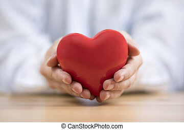 Red heart in hands. Health insurance or love concept.