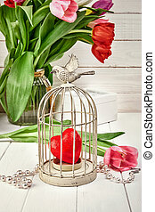 Red heart in iron cage with spring