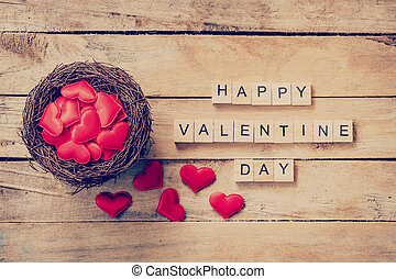 Red heart in nest with wooden text Happy Valentine Day on wood table background.