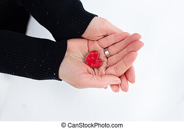 Red heart in the hands of a girl on a light background.