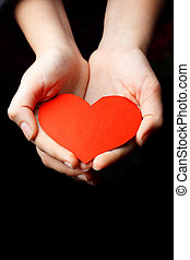 Red heart in the palms of a child against a dark background.
