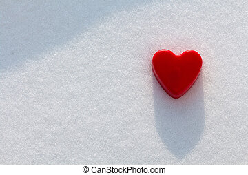 Red heart in the snow with sunshine