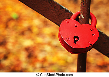 Red heart lock against the background of yellow autumn foliage