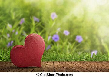 Red heart lying on wooden floor