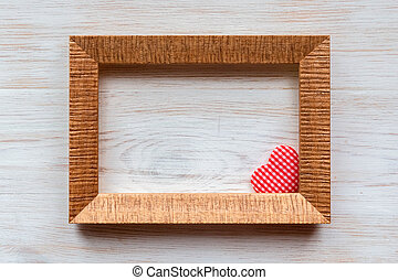 Red heart of handmade striped fabric in wooden frame corner on vintage white painted wooden background