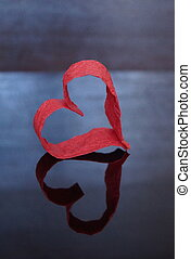 Red heart of paper on a dark background