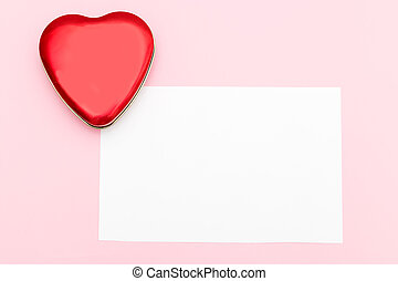 Red heart on a pink background and place for an inscription. Flat lay