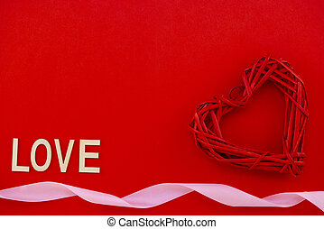 red heart on a red background with the inscription Love in wooden letters