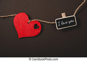 Red heart on a rope and small blackboard with text I love you on a black background. Valentine's day composition.