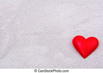 Red heart on a sand background