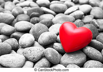 Red heart on pebble stones