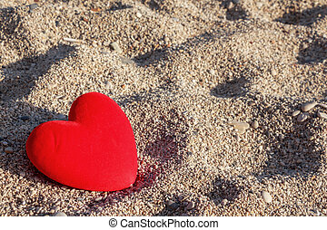 Red heart on the beach with small pebbles background.