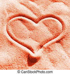 Red heart on the sand