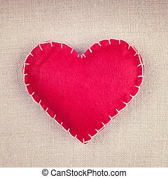 Red heart on vintage fabric background