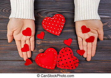 Red Heart on woman hand on wooden background with copy space. Concept for valentines day celebration or couple of love. Love concept