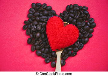 Red heart on wooden spoon and coffee beans romantic love valentines day on red background top view / love coffee concept