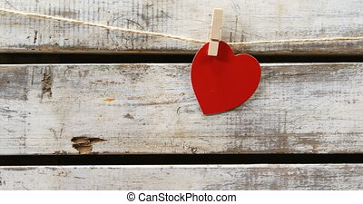 Red heart paper cut pinned on the rope against wooden surface 4k
