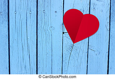 Red heart paper on blue wood table