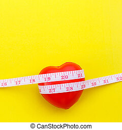 Red heart shape and white measurement tape on yellow...