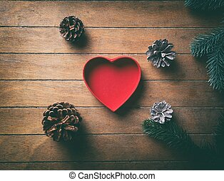 Red heart shape box and pine cones with branches on wooden ...