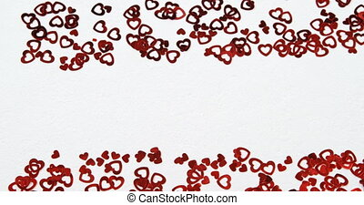 Red heart shape confettis on white surface. Scattered confetti 4k