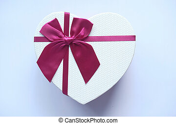 Red heart shape gift box isolated on white.