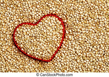 Red heart shape on uncooked quinoa background