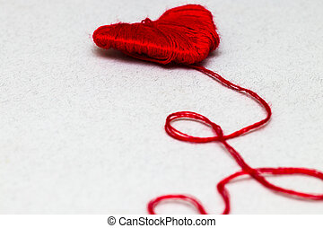 Red heart shape symbol made from wool isolated on white
