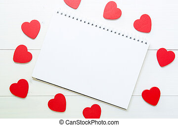 Red heart shape texture with love and notebook on wooden white background, 14 February Valentine day on grunge wood, copy space with note or diary writing text for you, celebration and holiday concept, top view.
