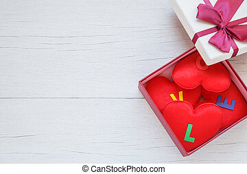 Red heart shape with love word in gift box with ribbon on white wooden plank background