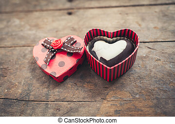 Red heart shaped box of chocolates on wooden background.