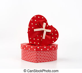 red heart-shaped cardboard box with bow on white background